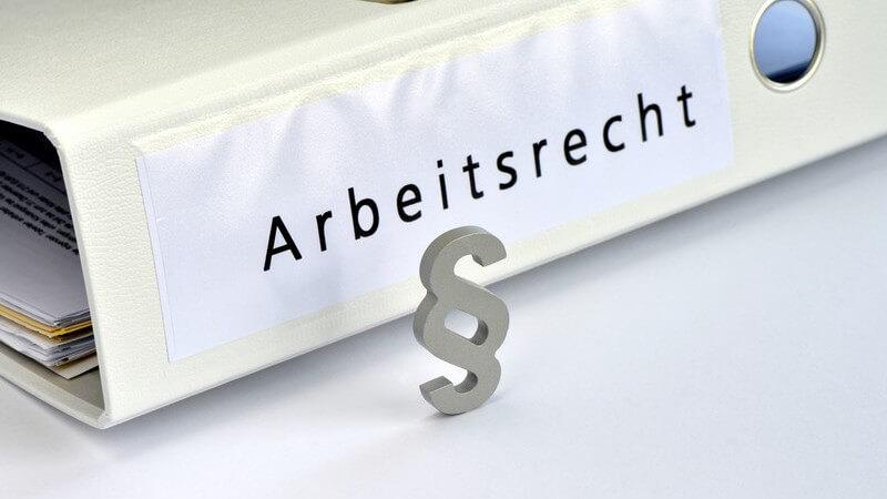 """Graues Paragraphenzeichen steht vor einem weißen Aktenordner mit der Aufschrift """"Arbeitsrecht"""""""