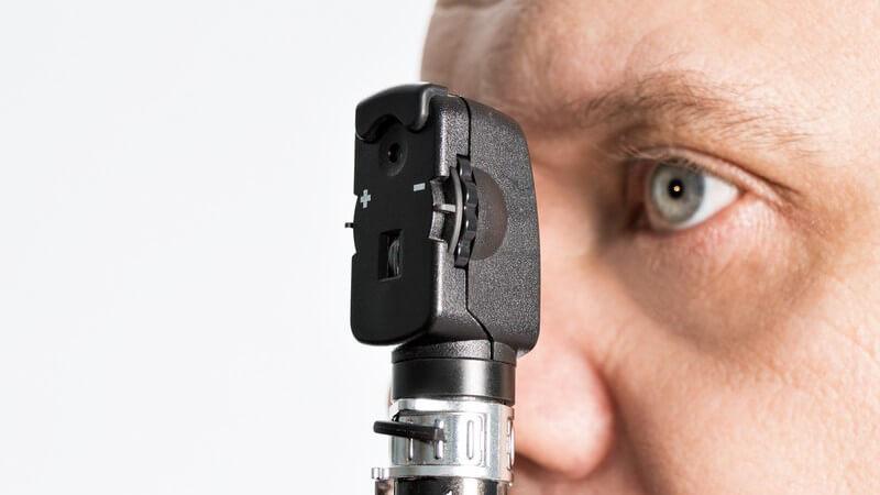 Mann guckt mit seinem linken Auge in ein kleines augenärztliches Untersuchungsgerät