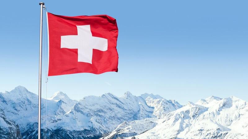 Wehende Schweizer Flagge an einem Mast vor Bergpanorama