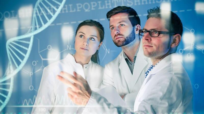 Drei Genetiker in weißen Kitteln stehen an einem Medienscreen