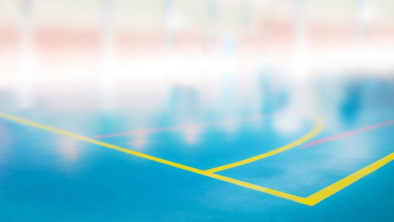 Boden einer Sporthalle mit markiertem Spielfeld für Ballsport