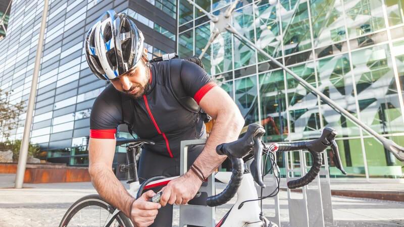 Mann mit Fahrradhelm und Radkleidung schließt sein Rennrad vor einem gläsernen Hochhaus ab