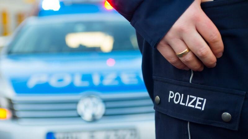 Ausschnitte eines Polizisten, im Hintergrund Polizeiauto, Fahrzeugkontrolle