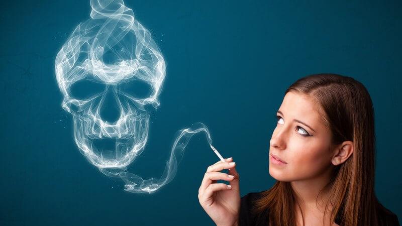 Zigarette rauchende Frau blickt zu einer Dunstwolke in Totenkopfform
