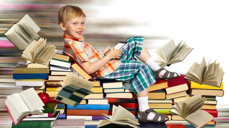 Junge in kariertem Hemd und Bermuda sitzt inmitten eines großen Bücherstapels