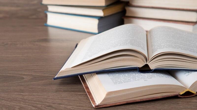 Lesen - aufgeschlagene, im Hintergrund gestapelte Bücher