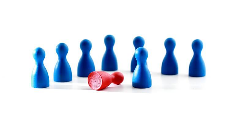 6 blaue Mensch-Ärger-Dich-Nicht-Männchen, in der Mitte ein Roter umgefallen