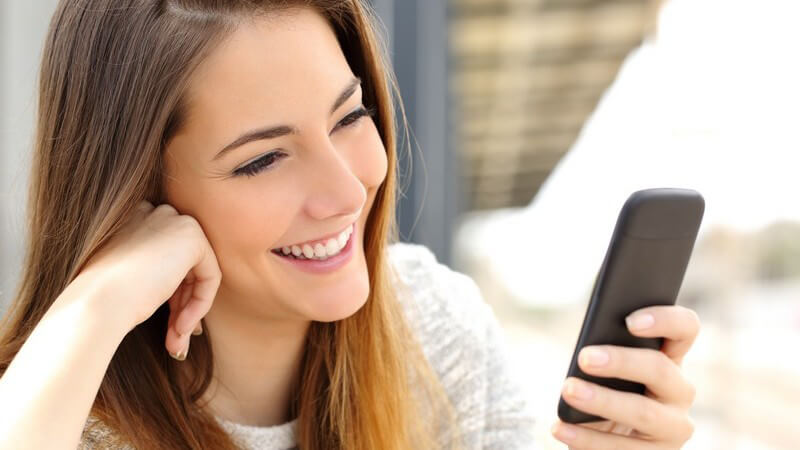 Junge Frau mit langen braunen Haaren nutzt lachend ihr schwarzes Smartphone