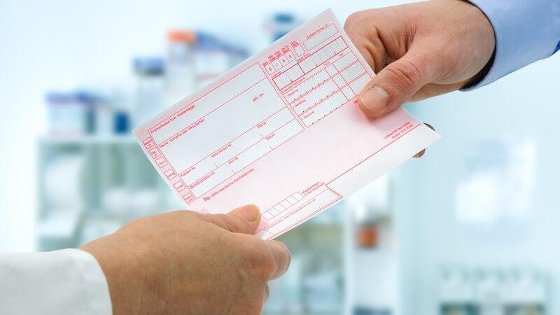 Arzt und Patient halten ein leeres Rezept in einer Arztpraxis