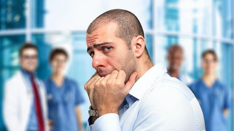 Ängstlicher Mann steht mit den Händen im Mund vor einem Krankenhaus, im Hintergrund vier medizinische Angstellte