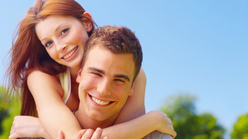 Junges Paar draussen, sie umarmt ihn von hinten, beide lächeln