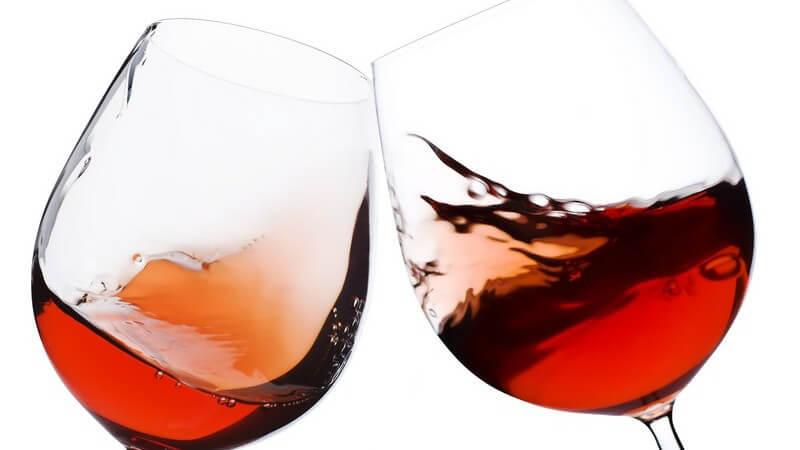 Nahaufnahme zwei Weingläser mit Rotwein beim Anstoßen