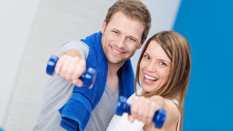 Junges Paar beim Fitnesstraining, er mit blauem Handtuch um den Hals, halten beide eine blaue Hantel in die Kamera