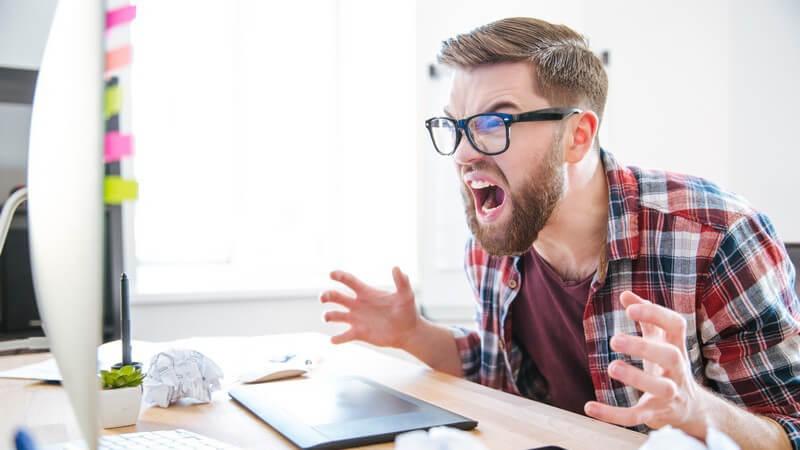Junger Designer mit Brille und Hipsterbart sitzt am Schreibtisch vor dem Bildschirm und rastet aus