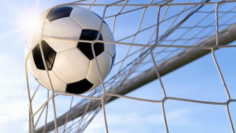 Fußball im Netz des Fußballtors unter blauem Himmel