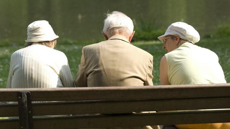 Rückansicht drei Senioren sitzen auf Bank im Park