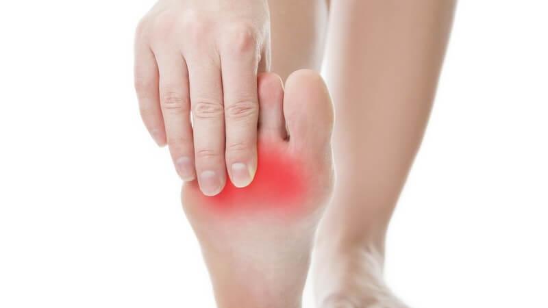 Frau hebt und fasst sich an den rechten Fuß, Schmerzen im Vorderfuß rot gekennzeichnet