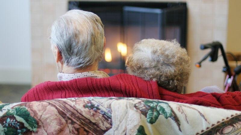 Rückenansicht altes Paar zusammen auf der Couch vor Kamin
