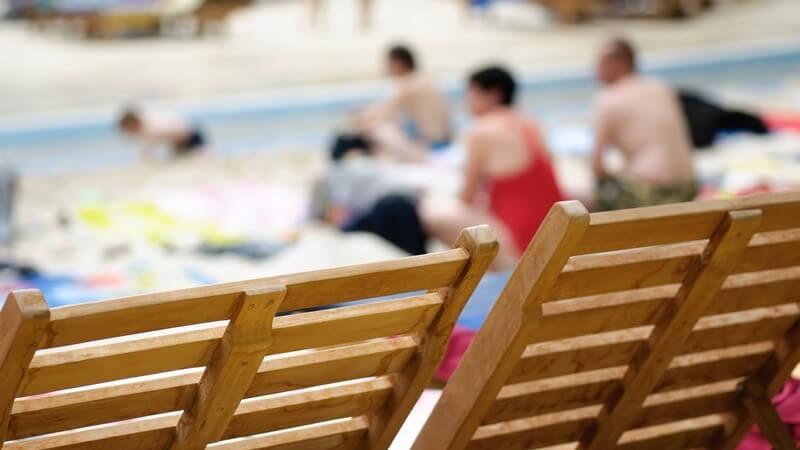 Nahaufnahme Liegestühle, im Hintergrund Menschen am Strand