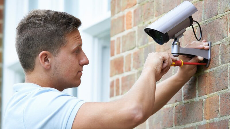 Mann montiert eine Überwachungskamera an einer Hauswand