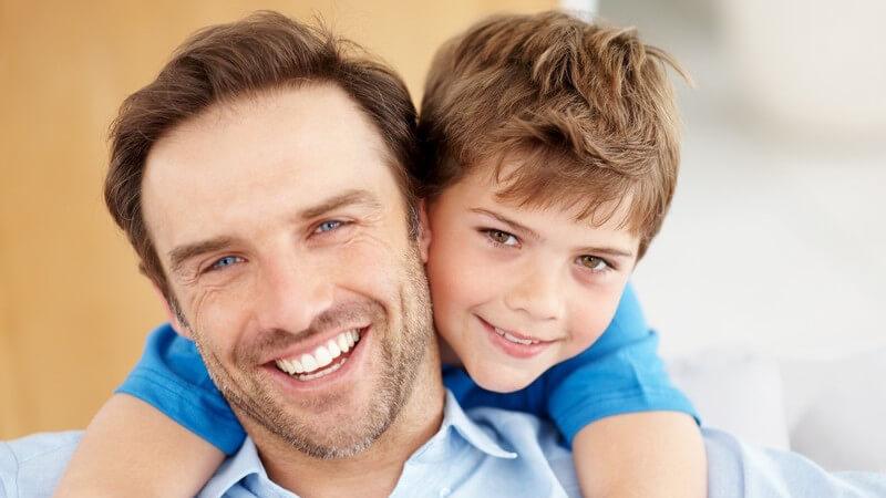 Junger Sohn umarmt Vater von hinten, beide lachen fröhlich