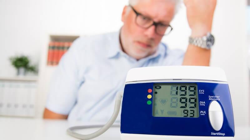 Älterer Herr mit Brille sitzt hinter einem Blutdruckmessgerät, das einen hohen Blutdruck von 199/99 anzeigt