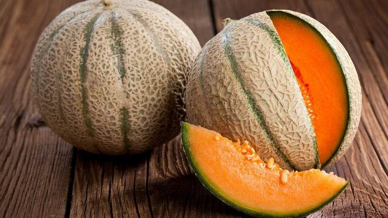 Intakte und geöfnete Cantaloupe-Melone auf dunklem Holz