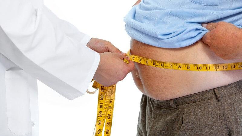 Arzt misst den Bauchumfang eines Mannes mit gelbem Maßband