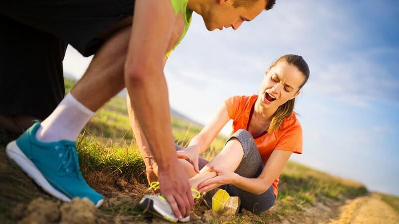 Paar beim Joggen: Frau hat sich verletzt und hat Schmerzen, sie hält sich den Knöchel, verdrehter Fuß