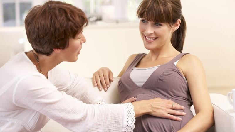 Schwangere Frau sitzt auf einem weißen Sofa und wird von einer Hebamme umsorgt
