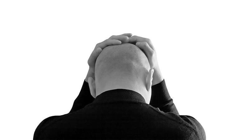 Schwarz-weiß Bild Rückenansicht Mann hält sich die Hände auf Kopf, Glatze