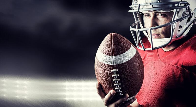 American Football-Spieler in rotem Trikot und weißem Helm hält einen Football in der Hand, Flutlicht im Hintergrund