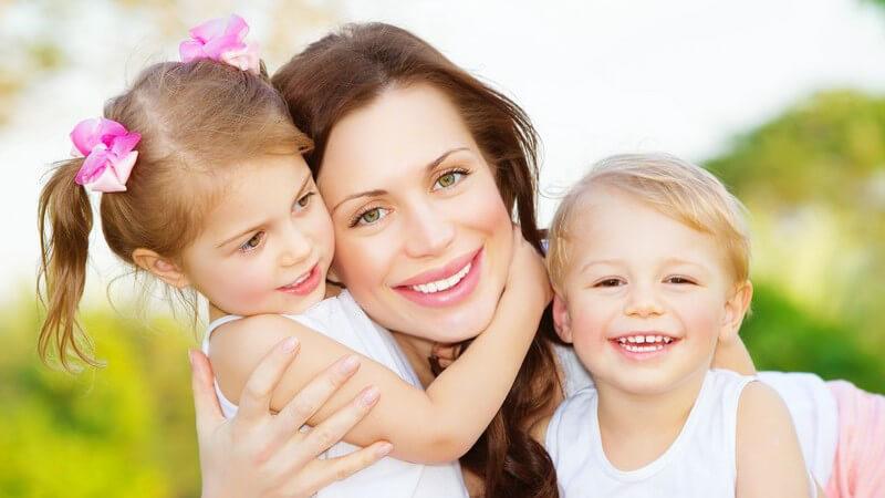 Junge Mutter mit Kindern, Zwillingen im Arm, draußen, alle drei lachen