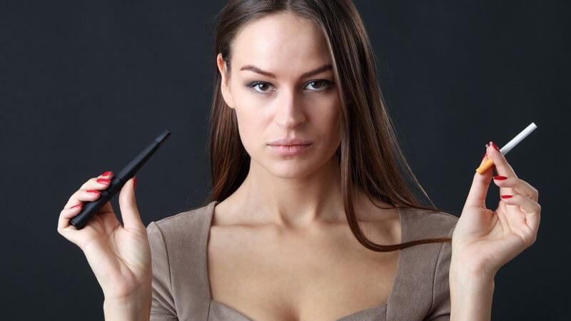 Dunkelhaarige Frau vor schwarzem Hintergrund hält in einer Hand eine E-Zigarette und in der anderen eine Tabakzigarette