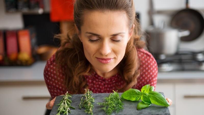 Frau riecht in der Küche an vier frischen Kräutern auf einer grauen Steintafel