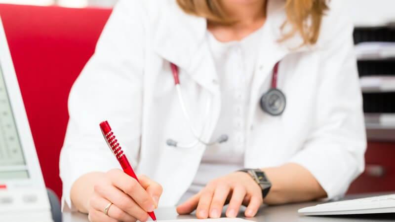 Ärztin sitzt auf rotem Stuhl in der Praxis und unterschreibt ein Attest
