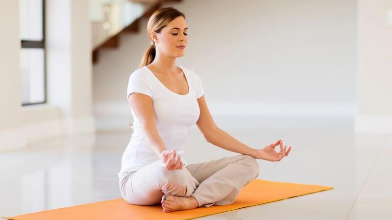 Junge Frau bei einer meditierenden Yoga-Übung auf einer orangen Yogamatte