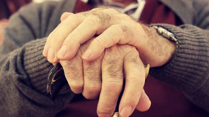 Alter Mann in Strickjacke hat beide Hände auf einem Gehstock