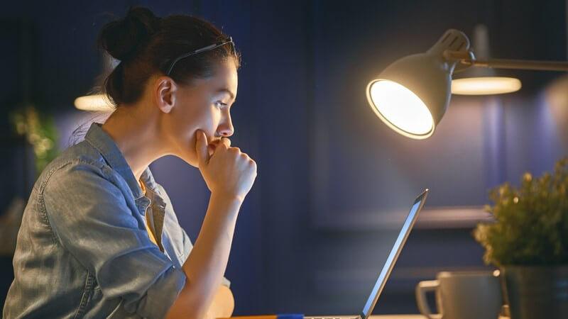 Dunkelhaarige Frau mit Brille im Haar arbeitet im Licht einer Schreibtischlampe am Laptop