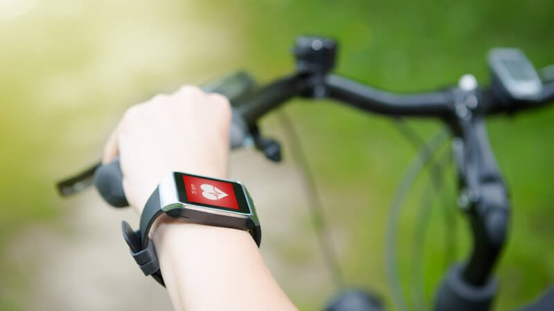 Arm mit Smartwatch zur Messung der Herzfrequenz während des Fahrradfahrens