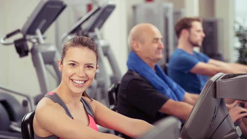 Lächelnde Frau trainiert im Fitness-Studio auf einem Ergometer, im Hintergrund trainieren auch noch zwei Männer