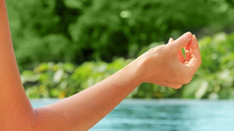 Ausgestreckter Arm einer am Wasser meditierenden Frau im Grünen