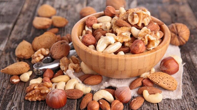 Gemischte Nüsse auf Holztisch und in kleiner Holzschale, unter den Nüssen liegt ein Nussknacker