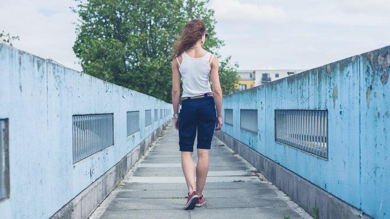 Junge Frau in kurzer Hose spaziert über eine schmale alte Fußgängerbrücke