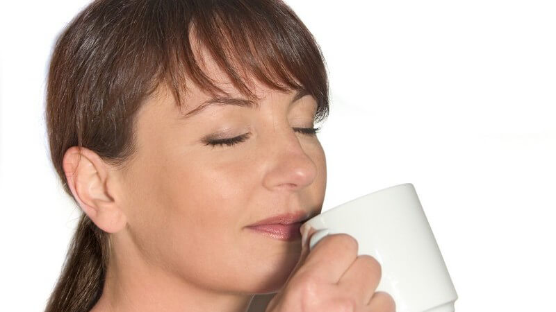 Dunkelhaarige Frau hält Kaffeebecher vor Nase und riecht den Duft mit geschlossenen Augen