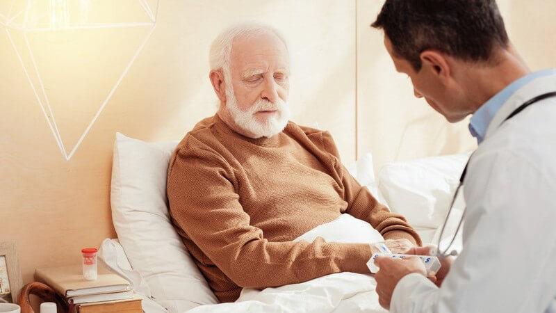 Arzt in weißem Kittel erklärt einem alten Mann mit grauem Vollbart am Krankenbett die vorgesehene Pilleneinnahme