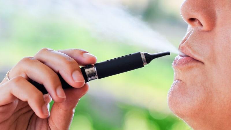 Gesicht eines Mannes, er zieht an elektronischer Zigarette, E-Zigarette