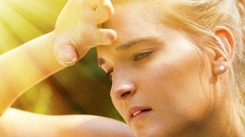 Junge Frau im heißen Sonnenlicht fasst sich erschöpft an die Stirn