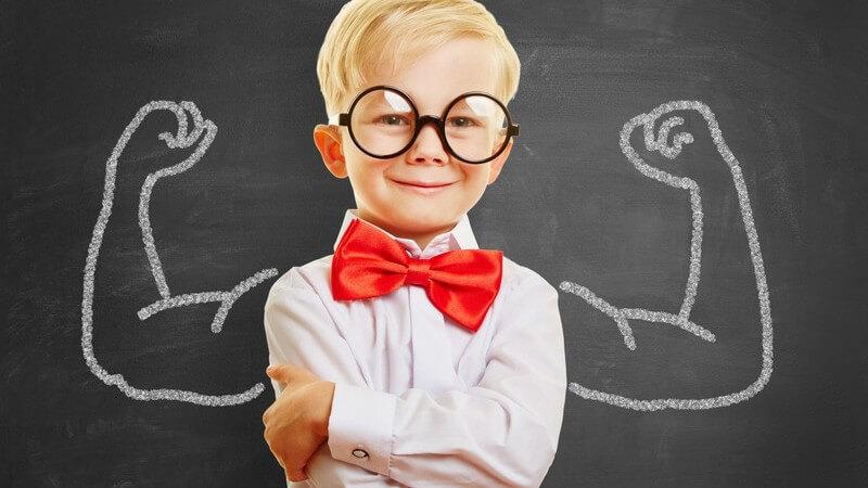 Blonder Junge steht mit Riesenbrille und roter Fliege vor einer Tafel mit angezeichneten muskulösen Armen