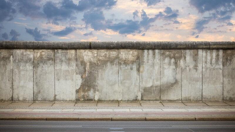 Die Berliner Mauer entlang einer Straße bei Sonnenuntergang